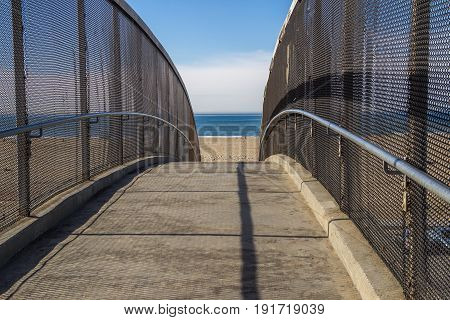 Foot bridge leading to beach and ocean with chain link fence