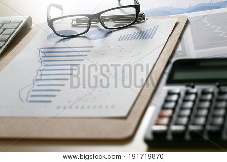 Business Reports  Teamwork On Table Report  Of Documents Blue Graphs And Charts Financial Paperwork