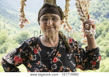 Portrait of an elderly woman picking dried queue garlic in balcony