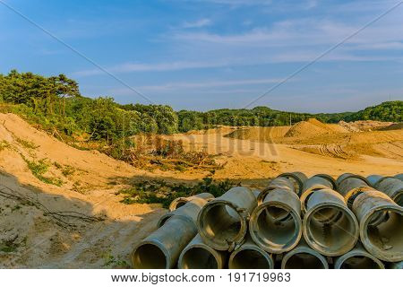 Landscape of land that has been cleared for development with large concrete drainage pipes stacked together in the foreground.