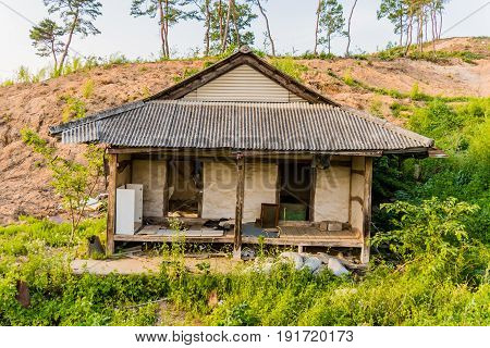 Old abandoned house in the countryside surrounded by green foliage with small dirt hill in the background.