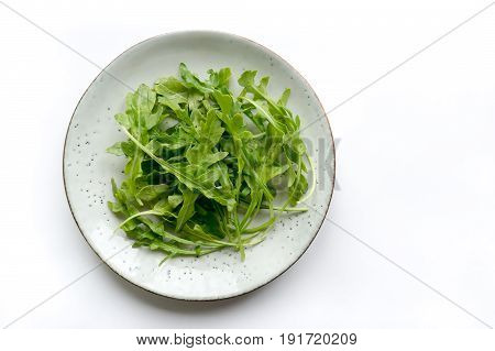 Fresh italian rucola leaves (arugula) on rustic plate. Top view