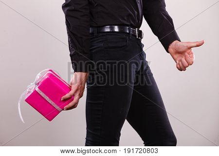 Man hiding pink gift box with ribbon behind back side view. Male hand holding christmas present giving thumb up sign. Birthday holidays and surprise.