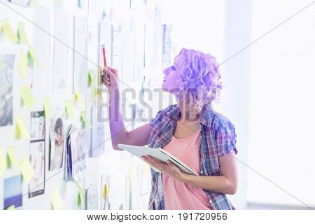 Creative businesswoman analyzing papers stuck on wall in office