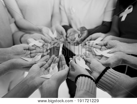 Group of hands holding pink ribbon for breast cancer awareness