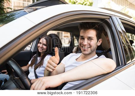 Smiling man in a car giving thumbs up