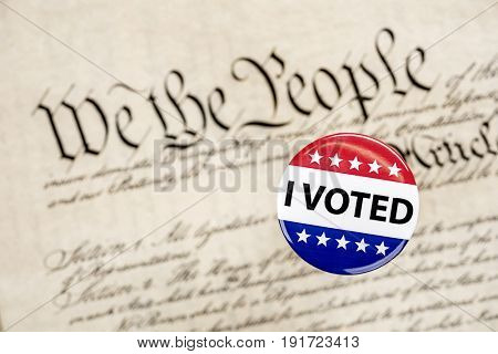 A vote badge hovers above the constitution as a symbol of an American citizen's constitutional right to vote.