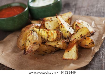 Spicy oven roasted potato wedges served on parchment paper