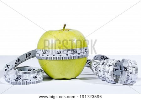 Green apple and measurement tape isolated on the white background