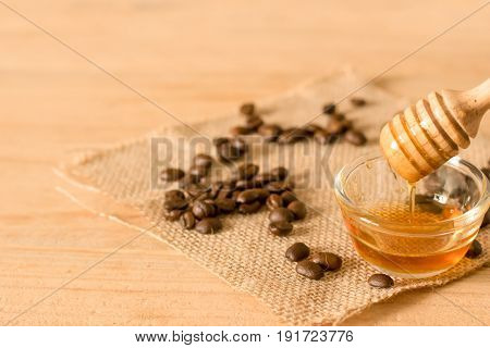 The Honey Dipper And Fragrant Honey Into A Transparent Bowl With Coffee Bean On Wooden Background.