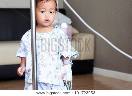 Little asia boy is stand and looking his parent in hospital room. Child with IV tube. recovering from sickness.