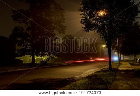 The residential block on an empty night street covered with fog, blurred lights of the city glows through a hazy haze