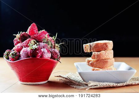 Strawberry and a cake on wooden table.