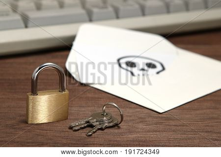 Lock and keys in front of envelope with skull written on card resting computer keyboard. Data protection and cyber security concept.