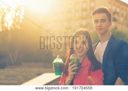 Teens drink fruit fresh from glasses. Love couple. Romance of first love.