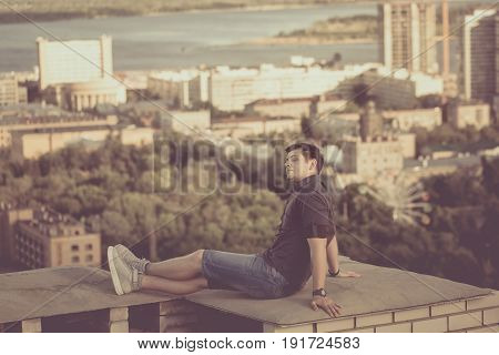 Roofer sits on the roof of a high-rise building and admires the clouds. Freedom and adrenaline. Toning.