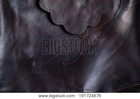 Surface seams and stitches of black leather.