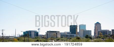 Panorama of downtown of a major Arizona city of Tucson full of high rise office buildings; back lit shot.
