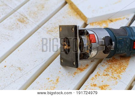 variable speed plunge router isolated on sawdust background