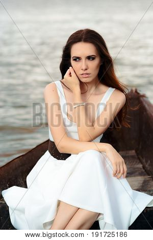 Sad Woman in White Dress Sitting in an Old Boat
