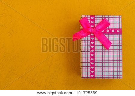 Top view on gifts box wrapped in striped gift paper decorated with ribbon.