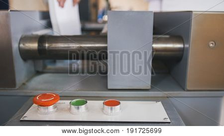 Red button on control panel of folding machine - printing polygraph industry, close up - telephoto