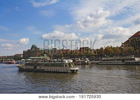 Prague - September 21 2016: Boats on Vltava river with historical buildings in background