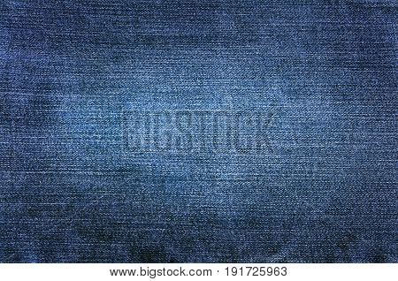 An abstract image of man made blue denim fabric.