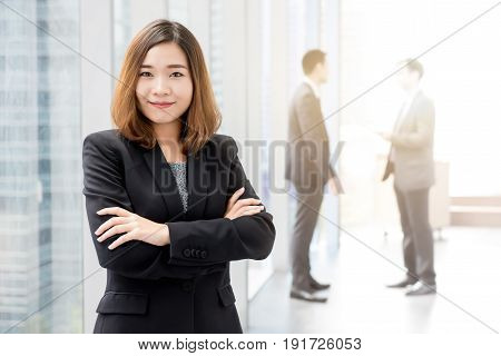 Confident Asian business woman standing and crossing her arms in office building hallway