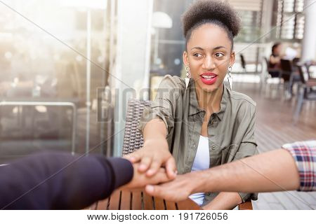 Young Afro woman joining hand together with her friends in stack empowering each other