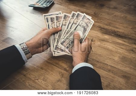 Businessman counting money Japanese yen banknotes at wooden table