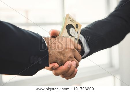 Businessman making handshake with money South Korean won banknotes in hands - bribery concept