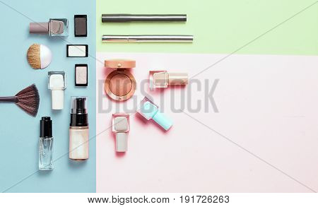 Creative flat lay of fashion bright nail polishes and decorative cosmetic on a colorful background. Minimal style. Copy space. Beauty blogger concept. Top view.