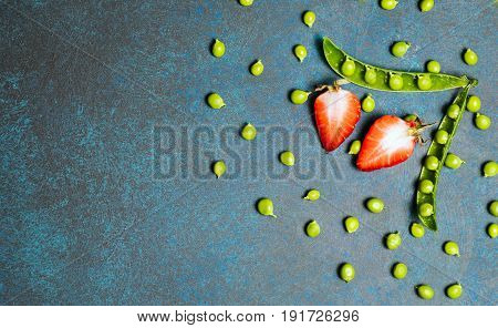 Strawberry amd green peas on vintage eco background. healthy eating concept. Flat lay, top view.