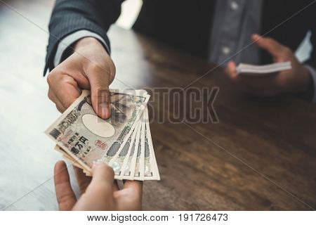 Businessman giving money Japanese yen banknotes to his partner - payment loan and bribery concepts