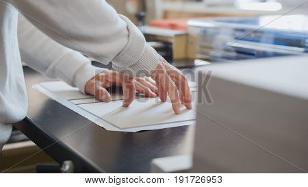 Worker works at polygraph machine, printing industry, close up