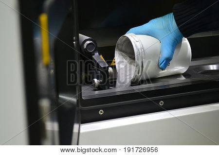 man pours metal powder into the chamber of a laser sintering machine. 3D printer printing metal. Modern additive technologies 4.0 industrial revolution
