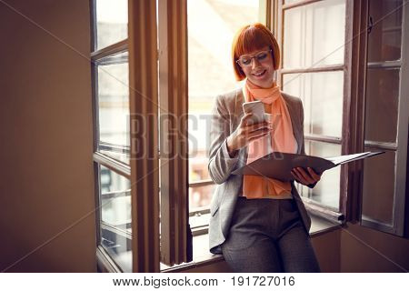 Businesswoman in office with cell phone contact business partner