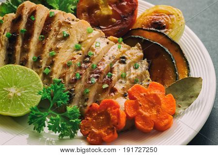 Sliced chicken breast barbecue on white plate served with grilled vegetable. Delicious chicken breast steak and salad for dinner. Homemade chicken breast barbecue on granite table background. Chicken steak or pork steak close up concept.