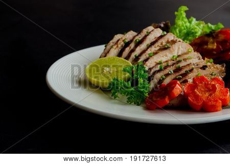Sliced chicken breast barbecue on white plate served with grilled vegetable. Delicious chicken breast steak and salad for dinner. Chicken breast barbecue on granite table for background. Chicken stake in extremely underexposed concept.