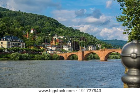 Carl Theodor Bridge And Nekkar River Embankment With Many Houses And A Hill At The Background On Sun