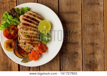Sliced chicken breast barbecue on white plate served with grilled vegetable. Delicious chicken breast steak and salad for dinner. Homemade chicken breast barbecue on wood table for background. Chicken or pork steak in top view concept.