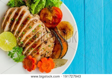 Sliced chicken breast barbecue on white plate served with grilled vegetable. Delicious chicken breast steak and salad for dinner. Homemade chicken breast barbecue on blue wood table for background. Chicken or pork steak in top view concept.