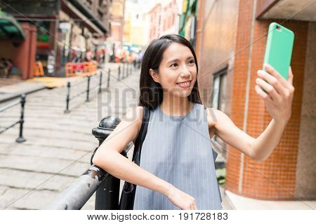 Woman taking selfie with mobile phone in Pottinger Street