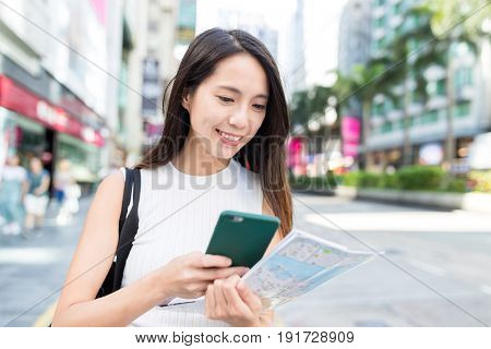 Woman use of cellphone and city map in Hong Kong city