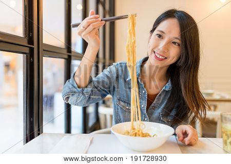 Asian Woman eating noodles in chinese restaurant