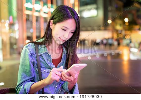 Woman use of smart phone in the city at night