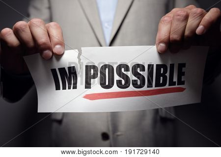 Businessman tearing the word impossible to make possible concept for self belief, positive attitude and  motivation