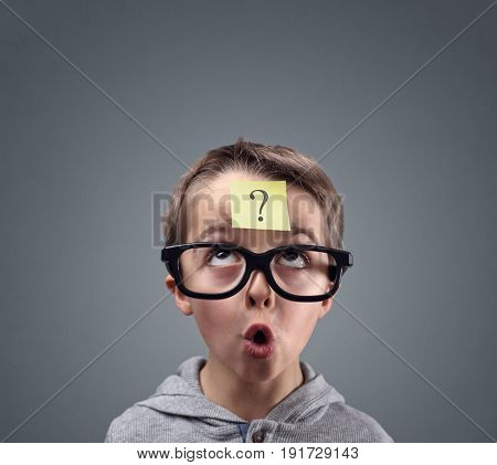 Confused boy thinking with question mark on sticky note on forehead poster
