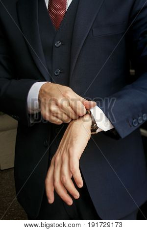 Man In Black Suit Puts His Sleeve Over A Watch
